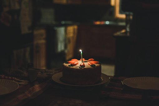 Photo of a round carrot cake  in a dark room with one lit birthday candle. | Photo: Getty Images