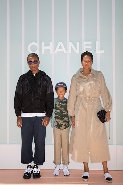 Pharrell Williams, left, Rocket Williams and Helen Williams attend the Chanel Cruise 2018/19 Replica Show at Sermsuk Warehouse Pepsi Pier on October 31, 2018, in Bangkok, Thailand. | Source: Getty Images.