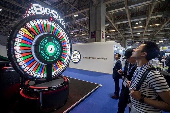 Attendees stand in front of a Big Six wheel of fortune at the Global Gaming Expo Asia (G2E Asia) in Macau, China, on Tuesday, May 21, 2019 | Photo: Getty Images