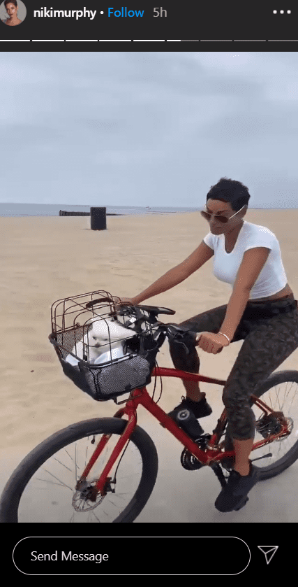 A photo of Nicole Murphy in a white T-shirt cycling with her puppy. | Photo: Instagram/Nikimurphy