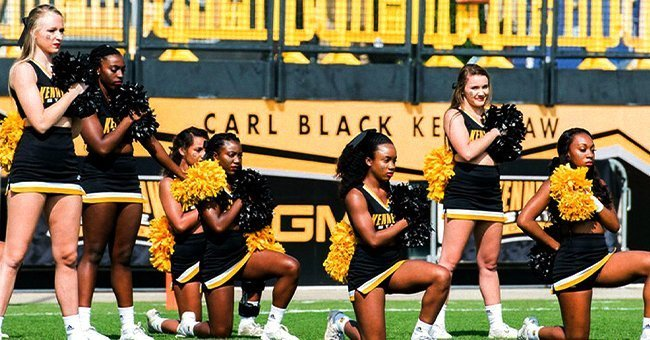 Tommia Dean and 4 other cheerleaders kneeling during a football game at KSU | Source: Twitter/wsbtv