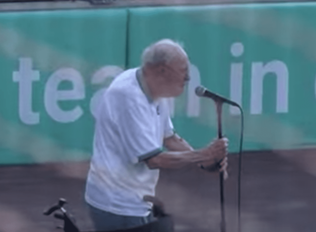 An elderly veteran holds the mic as he delivers a moving rendition of the national anthem at a baseball game | Photo: Facebook/wmwcaps