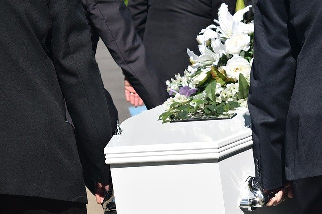 Pallbearers carry a white coffin with flowers on top | Photo: Pixabay
