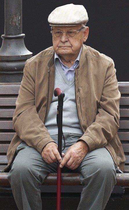 Anciano sentado en una banquilla sosteniendo un bastón. | Imagen: Max Pixel