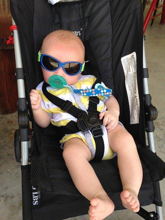 Un bébé dans une poussette avec des lunettes et une tétine. | Photo : Pixabay