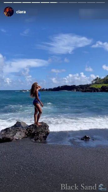 Ciara, dressed in a blue swimsuit and standing on a rock close to the ocean | Photo: Instagram/ciara