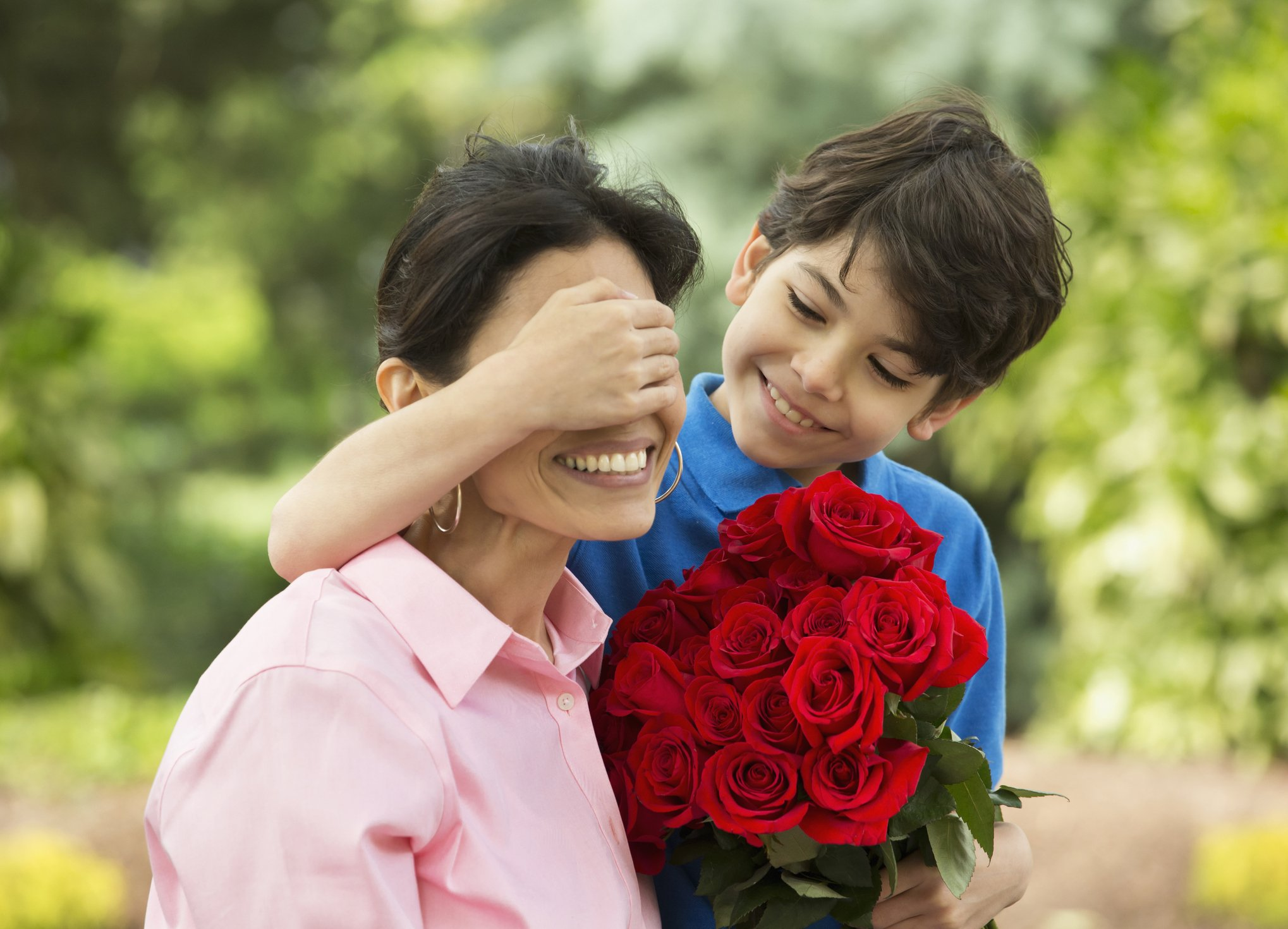 Hispanic boy giving mother bouquet of roses | Photo: Getty Images