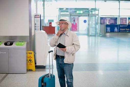 Photo of a elderly man standing in the airport terminal with his documentation, looking confusedly at the departure board | Photo: Getty Images