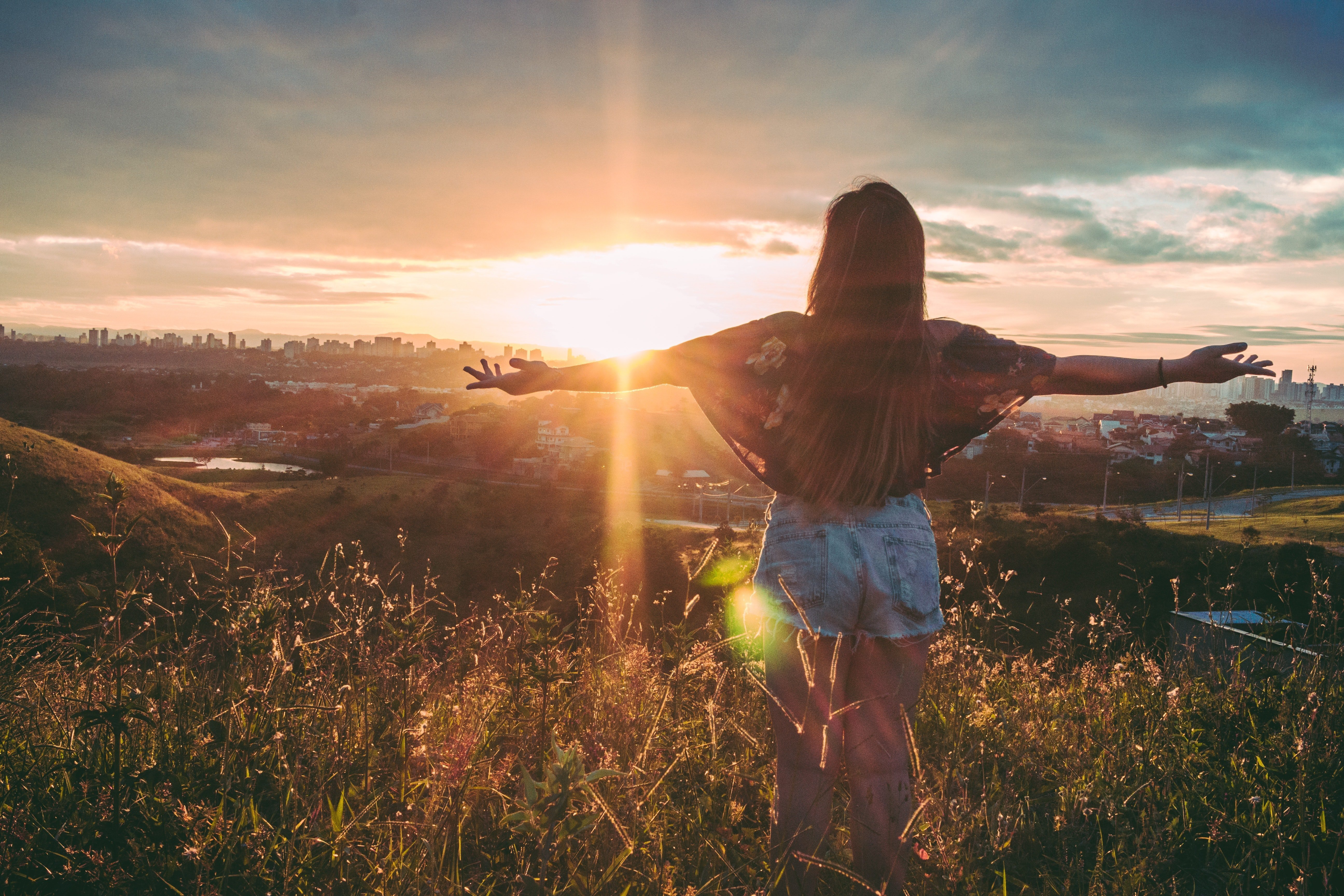 A woman enjoying freedom by spreading her arms against sunlight. | Source: Pexels