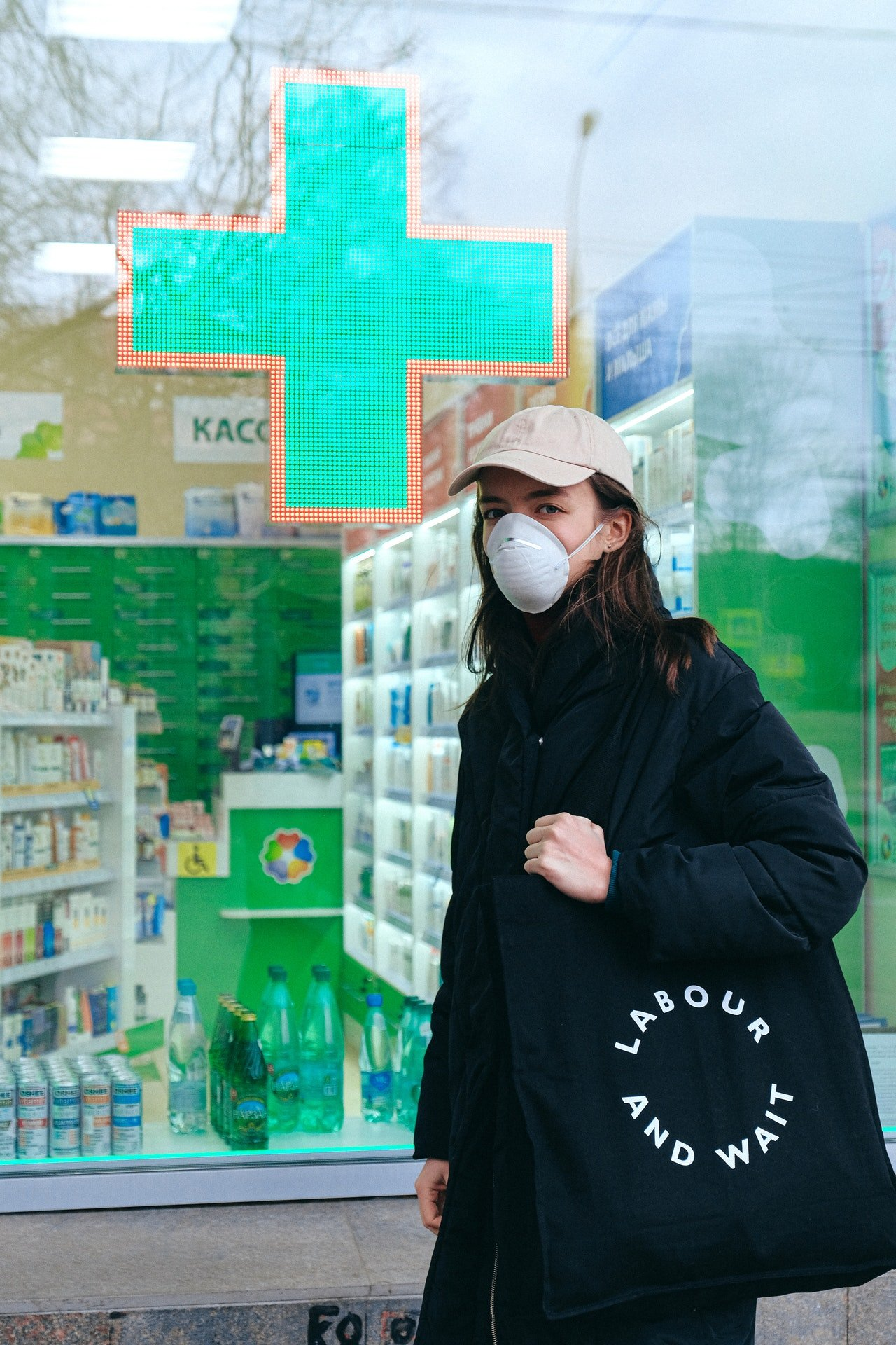 Photo of woman standing in front of a pharmacy store | Photo: Pexels