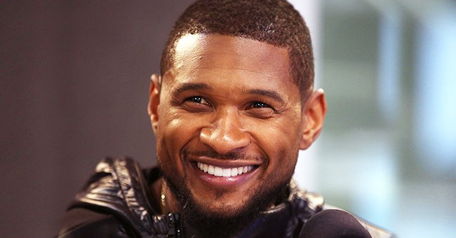 Usher's Girlfriend Posts Rare Pic Posing With Their Baby Sovereign in Front of a Purple Trailer