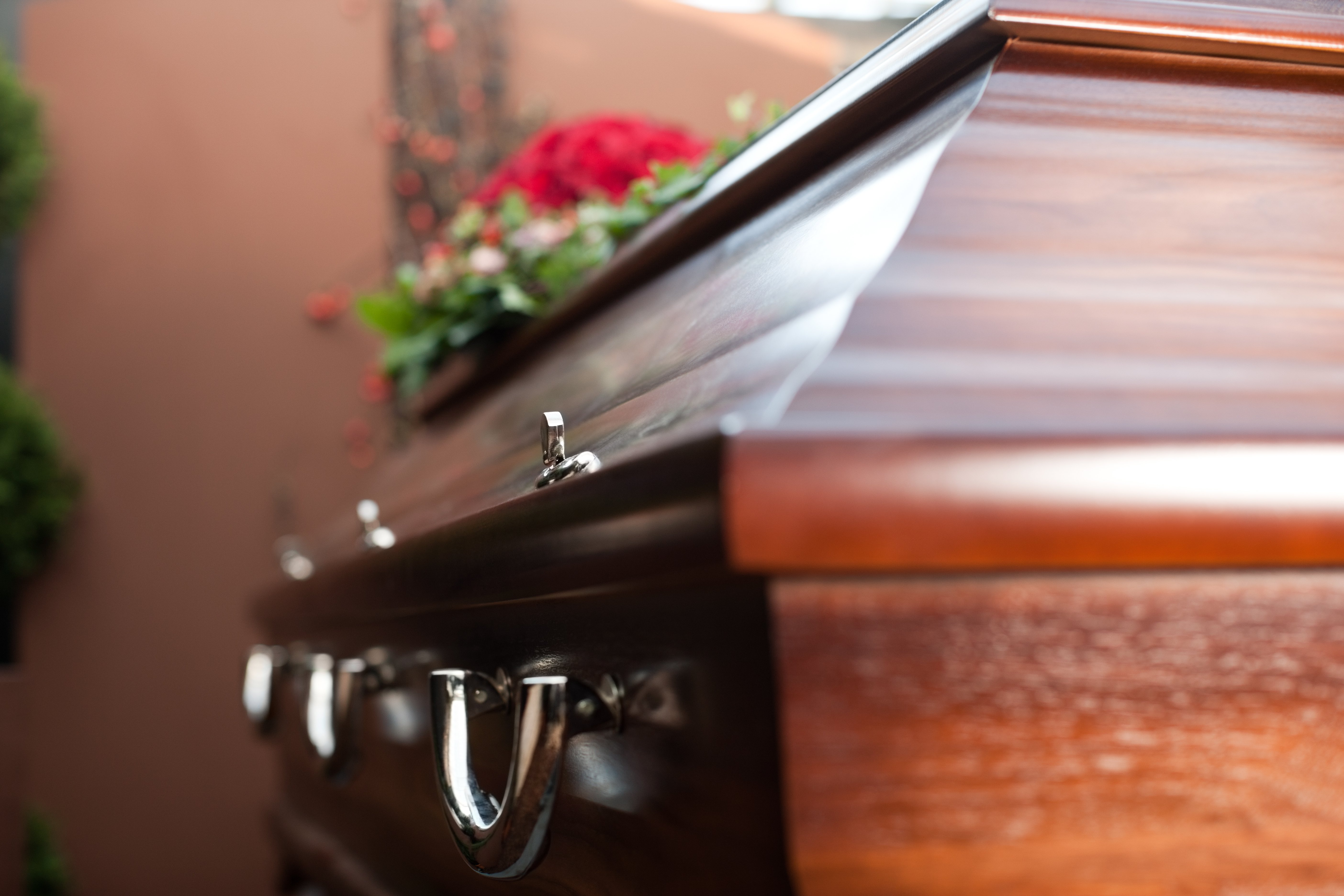 A coffin with red flowers on top. | Source: Shutterstock