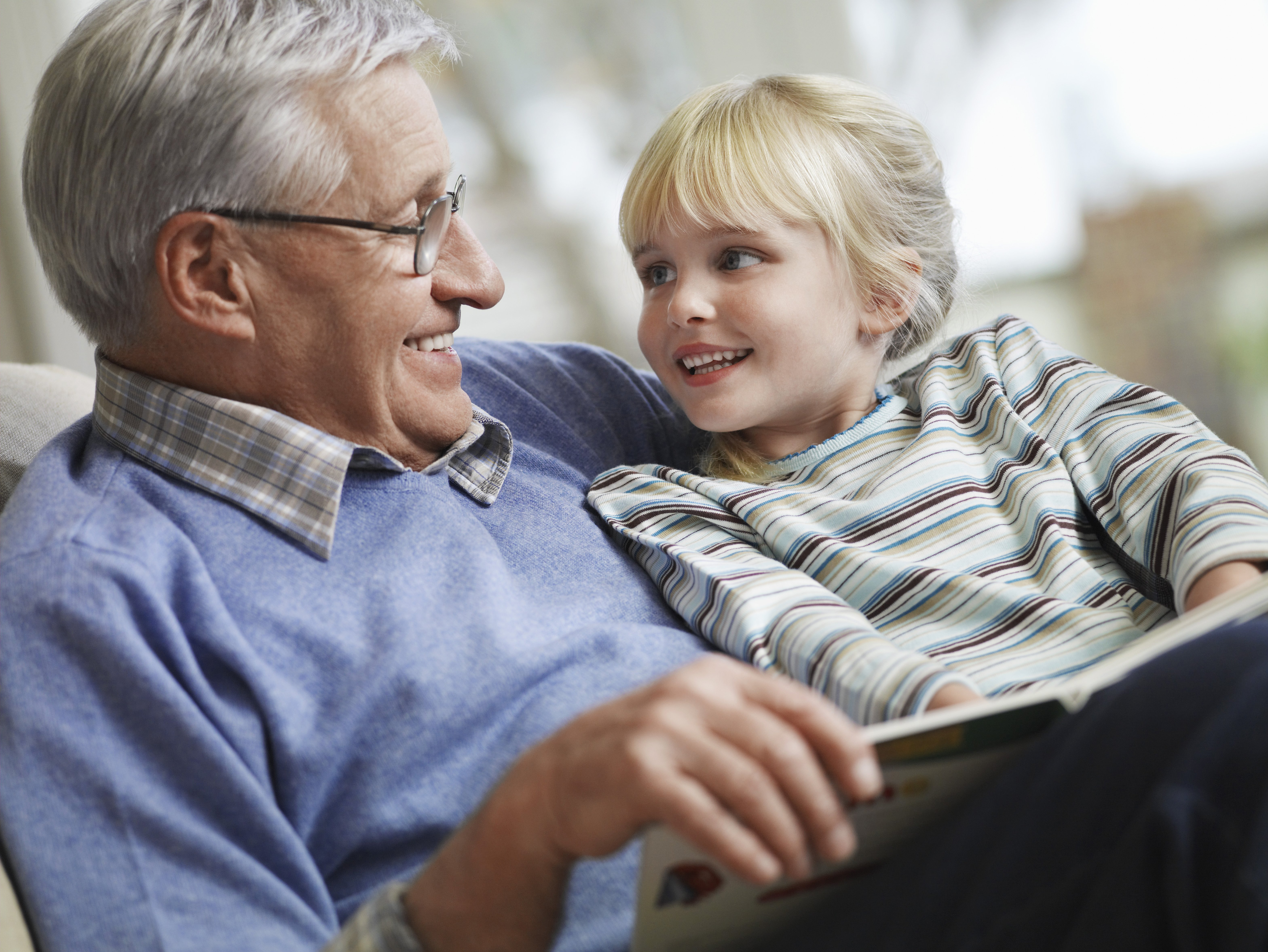 Happy little girl with grandfather reading story book at home | Photo: Shutterstock.com