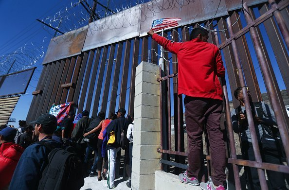 Migrants at the U.S.-Mexico border fence on November 25, 2018, in Tijuana, Mexico.| Source: Getty Images.