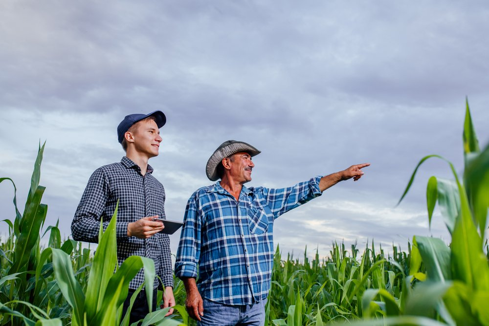 Two farmers discussing the size of their farms   Shutterstock