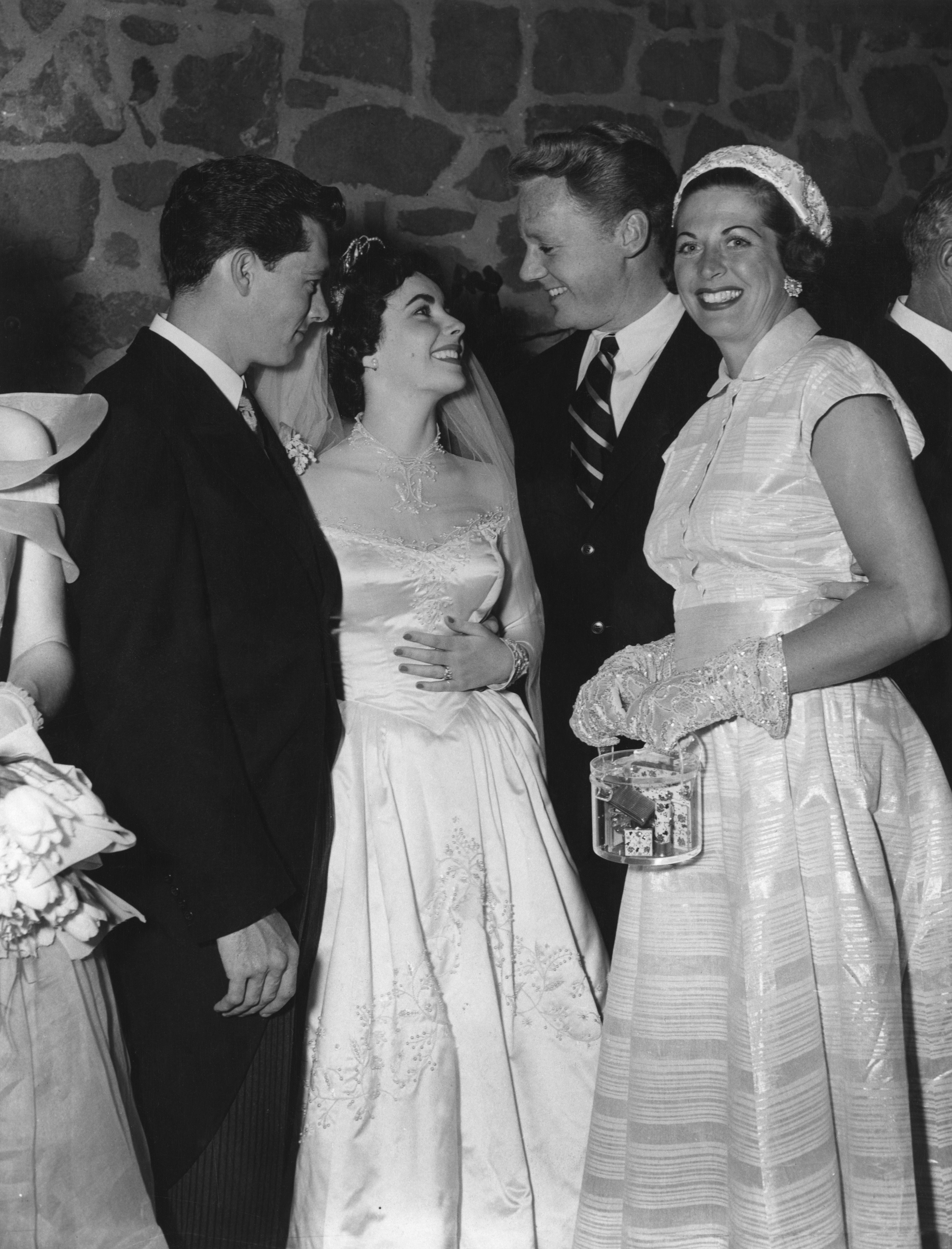 Screen star Van Johnson and his wife Evie (right) congratulate Elizabeth Taylor and her husband Conrad Hilton (left) at their wedding reception in Beverly Hills, Hollywood on 13th May 1950. | Source: Getty Images