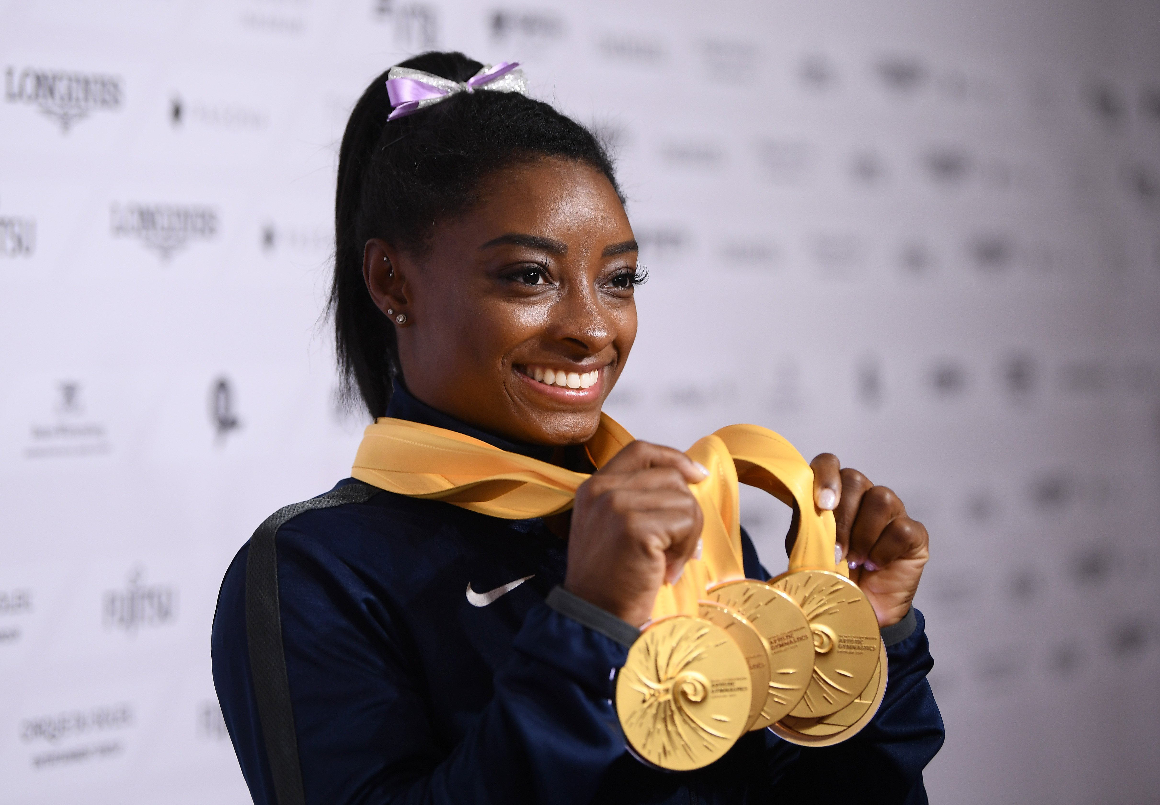 Simone Biles holding up her haul at the FIG Artistic Gymnastics World Championships in Stuttgart, Germany on October 13, 2019. | Photo: Getty Images