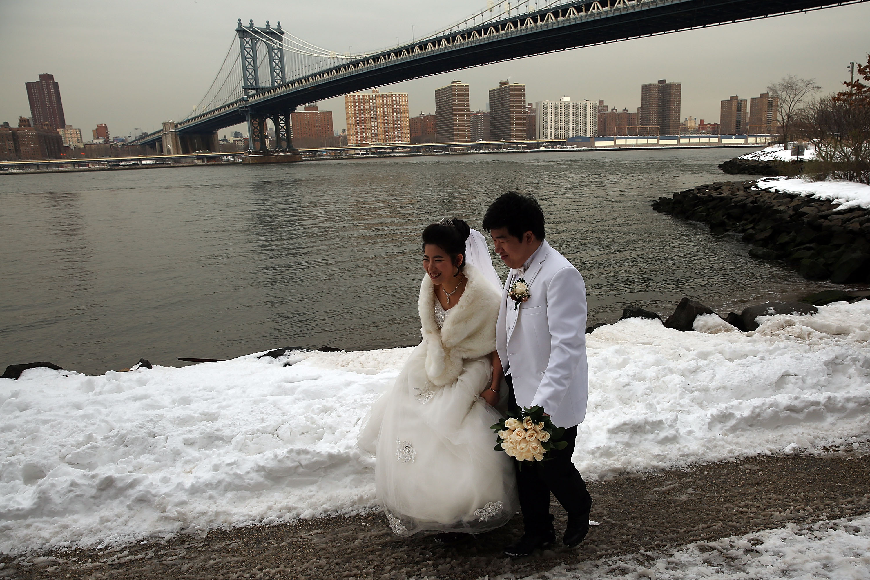 A newly married couple walk in the snow on the first workday following a blizzard that set a new single-day record for snowfall in both New York |Getty Images : photos