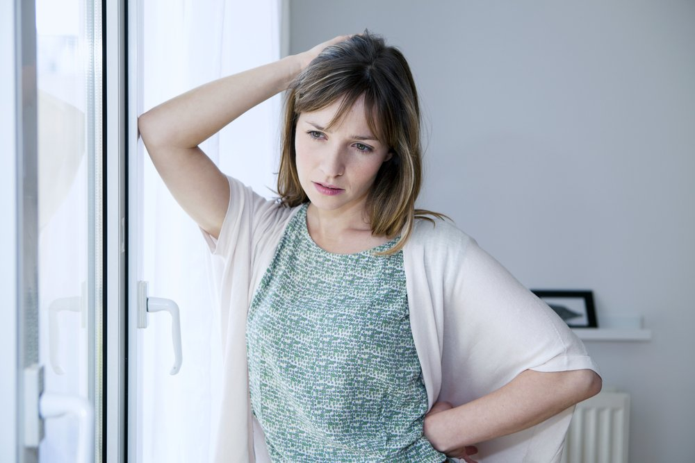 A photo of a worried woman standing by the windows.   Photo: Shutterstock