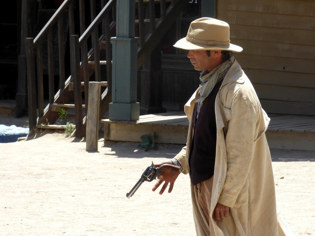 A cowboy standing outside while holding a gun in his hand   Photo: Pixabay/Pashi