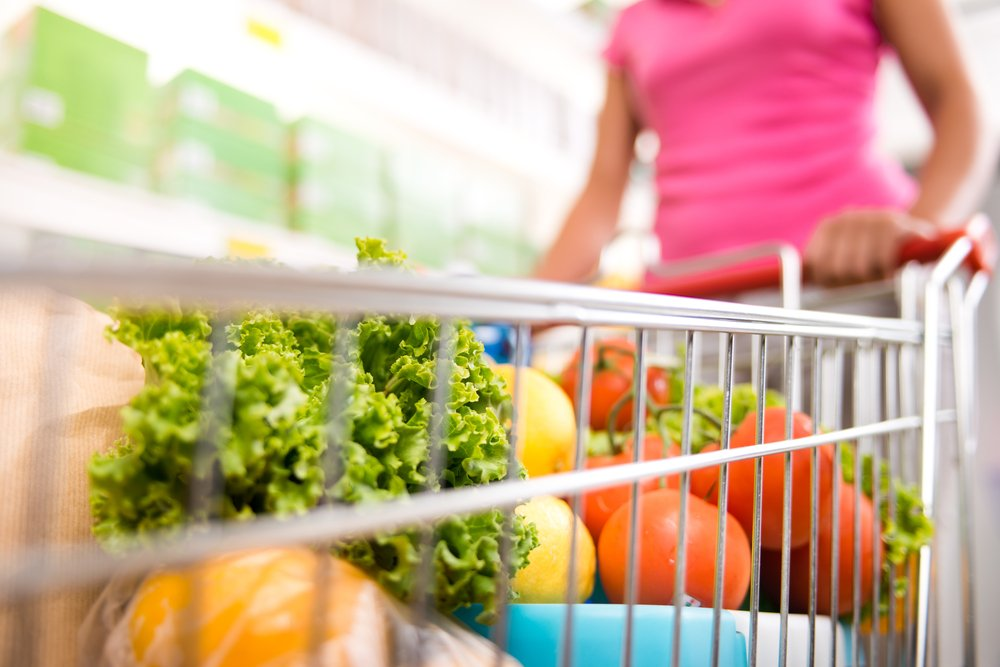 A photo of a woman with a shopping cart filled with fresh fruit and vegetables.   Photo: Shutterstock