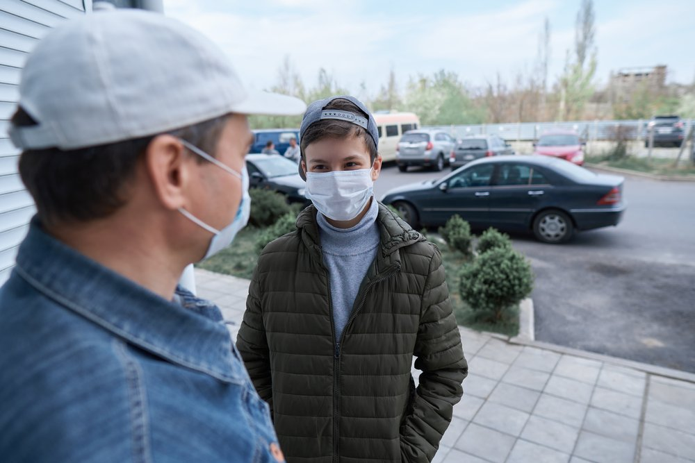 A man talks to a boy near a wall and closed-door while both wear medical masks on their faces | Photo: Shutterstock/s_oleg