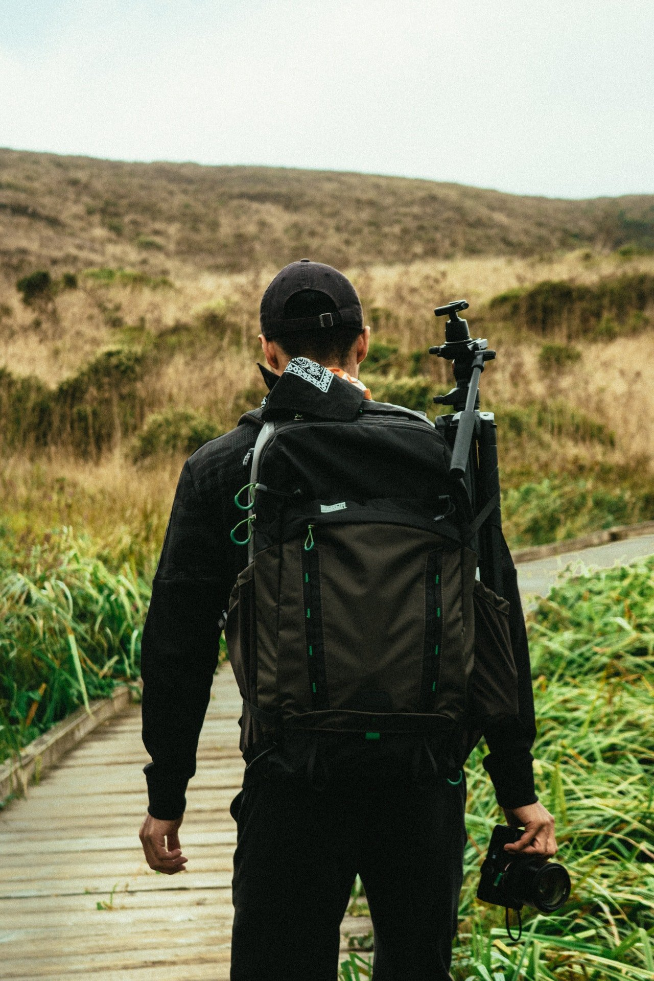 Photo of a man trekking while wearing a black backpack | Photo: Pexels