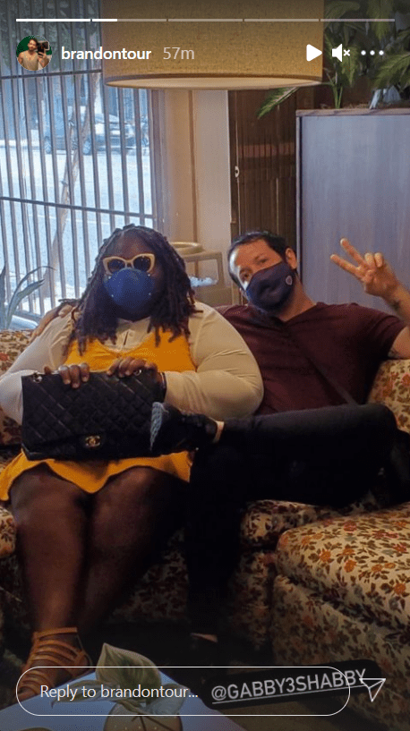Gabby Sidibe andBrandon Frankel sitting on a couch with facemasks on. | Photo: instagram.com/brandontour