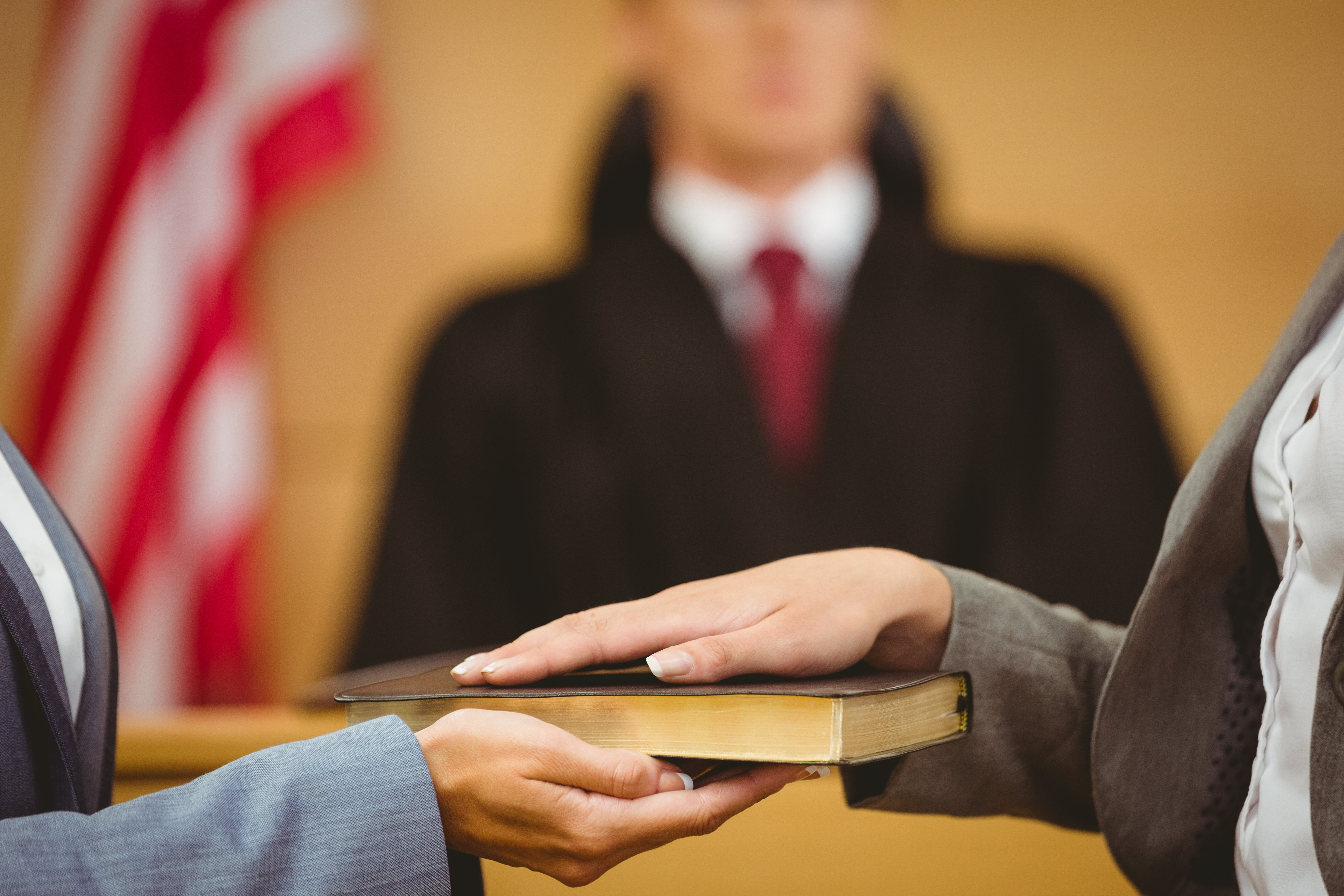Witness swearing on bible in court. Image Shutterstock