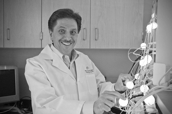 A scientist laughing next to a device. | Photo: Flickr
