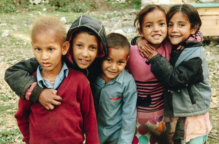 Des groupes d'enfants qui rient fixant le caméra | Photo : Unsplash