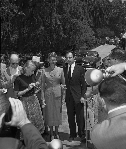 Rita Hayworth and Aly Kahn surrounded by reporters outside Hayworth's home, 1952. | Source: Wikimedia Commons