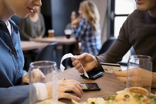 Close up couple with credit card paying bill calculating tip with smart phone in brewery restaurant | Photo: Getty Images