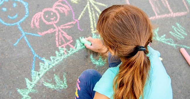 Little girl drawing pictures on the cement with chalk.   Source: Shutterstock