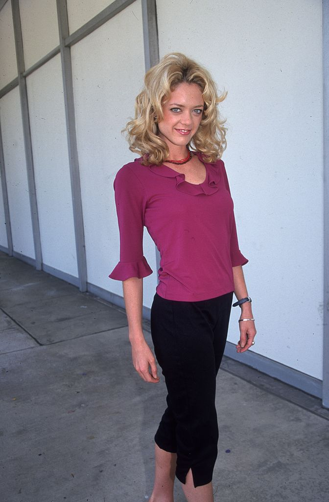 American actor Lisa Robin Kelly wearing a fuchsia blouse with a ruffled neckline and black Capri pants, standing on a film lot, Beverly Hills, California on  April 12, 2000 | Photo: Getty images