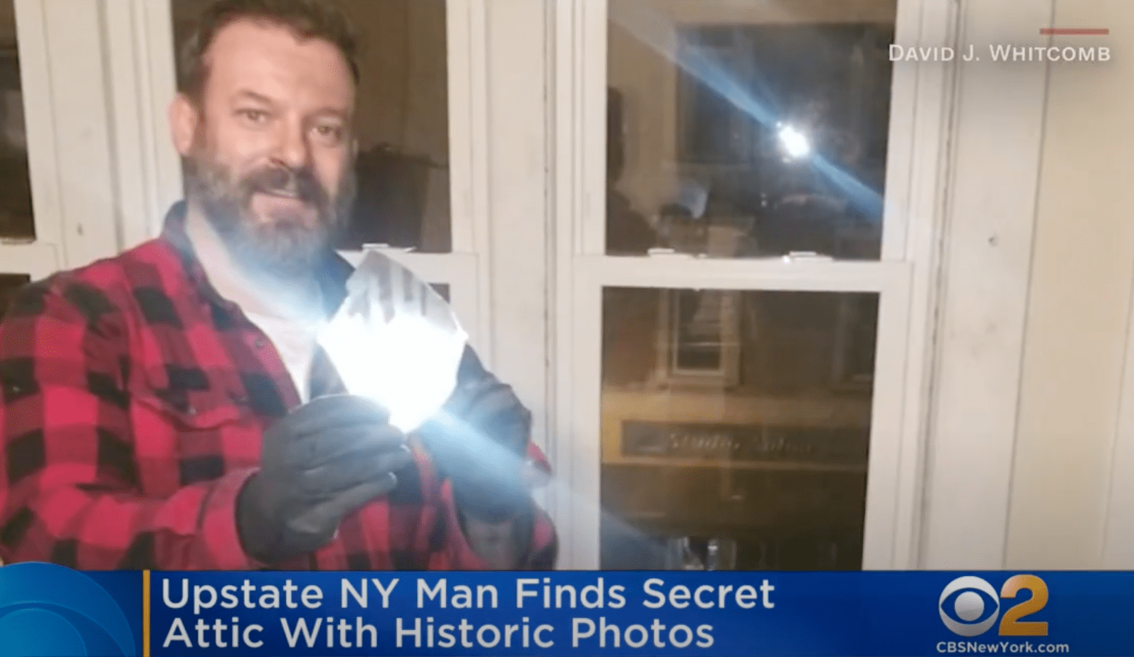 A man who discovered hidden treasures in his attic holds up a glass negative | Photo: Youtube/CBS New York