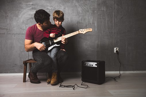 Photo of father and son playing guitar and singing in the microphone in the basement. | Photo: Getty Images