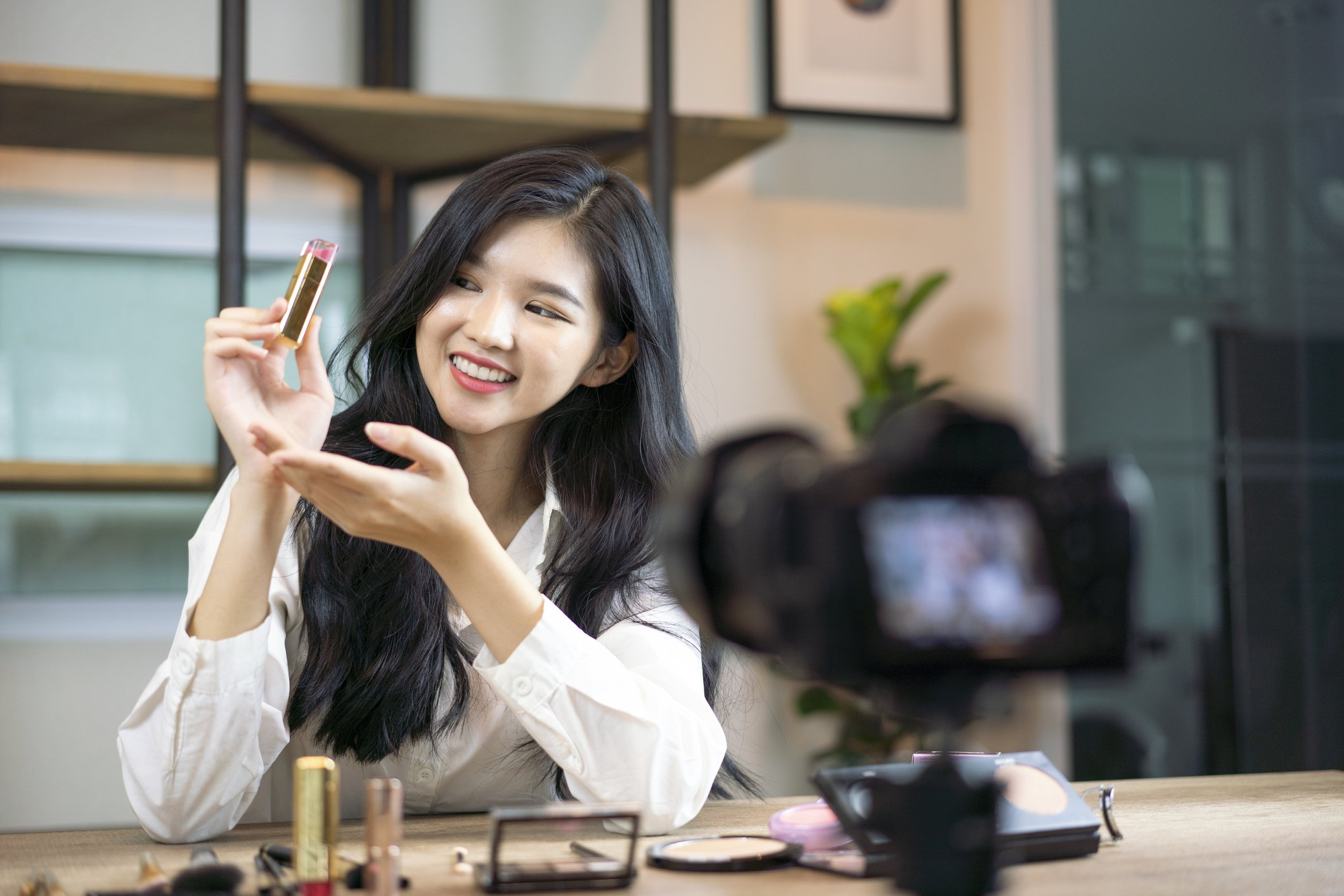 A young Asian female sits in front of personal camera and smiles as she holds up pink lipstick for a vlog video, Thailand | Source: Getty Images