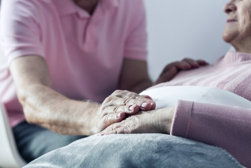 Senior man holding hand of his ill wife. | Source: Shutterstock.