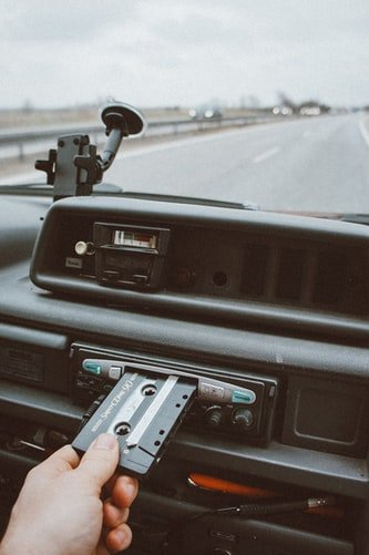 A man tries to listen to a tape as be drives in frustration | Photo: Unsplash
