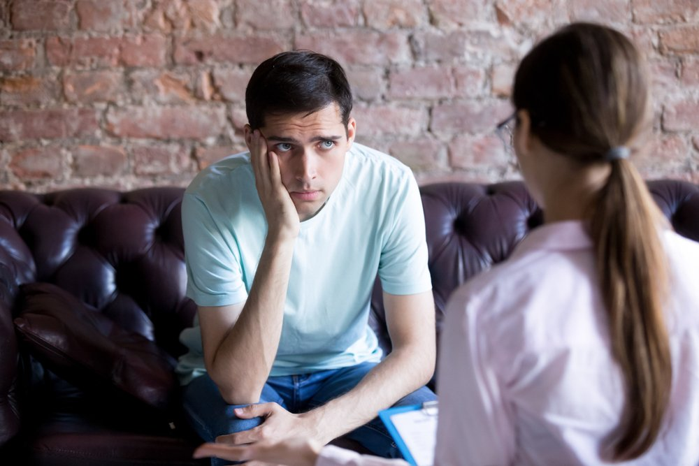 An unhappy male patient balancing his chin on his hand while listening to a psychiatrist for advice | Photo: Shutterstock/fizkes