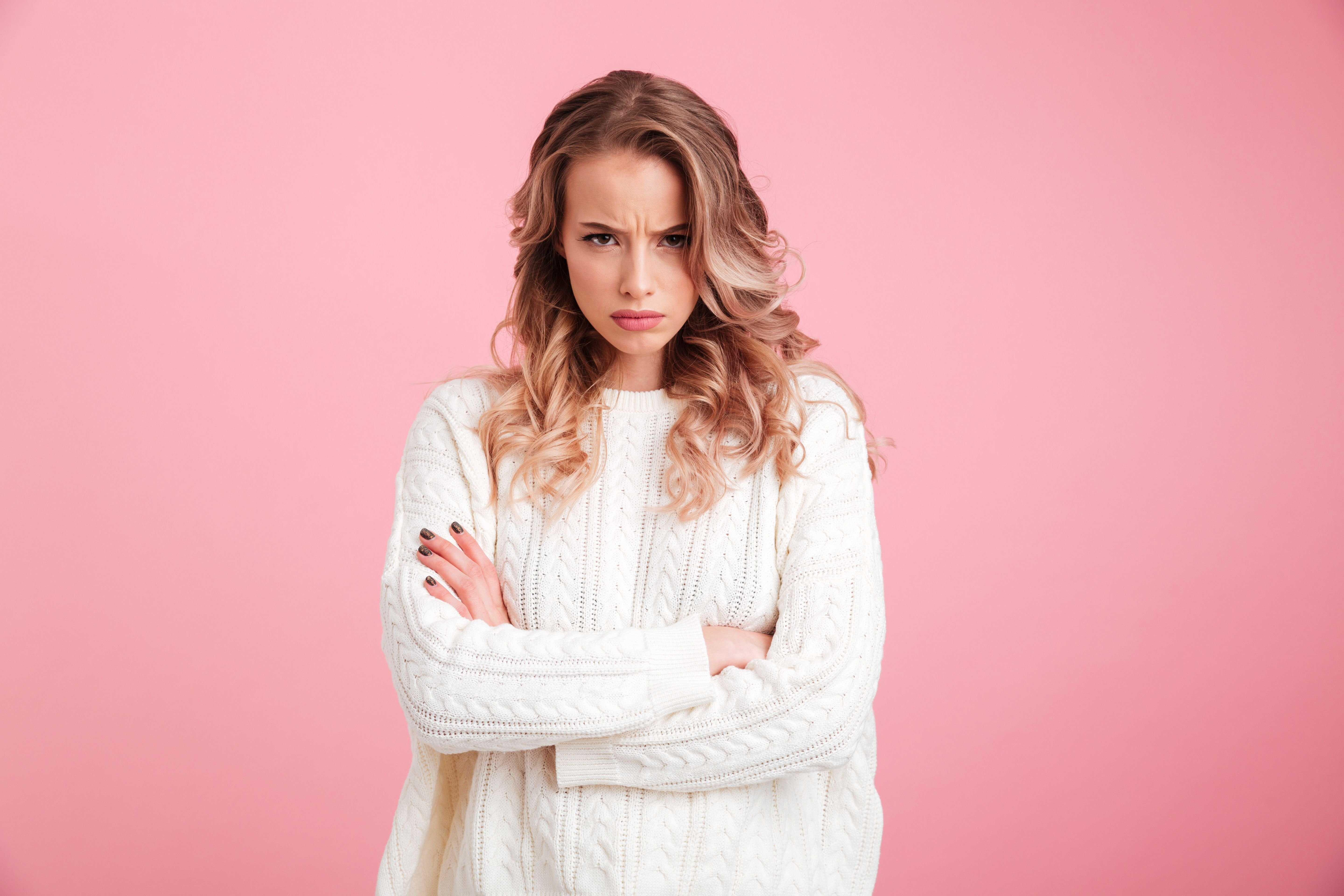 Blonde woman wearing a white jersey in front of a pink background crossing her arms and staring angrily into the camera.   Photo: Shutterstock