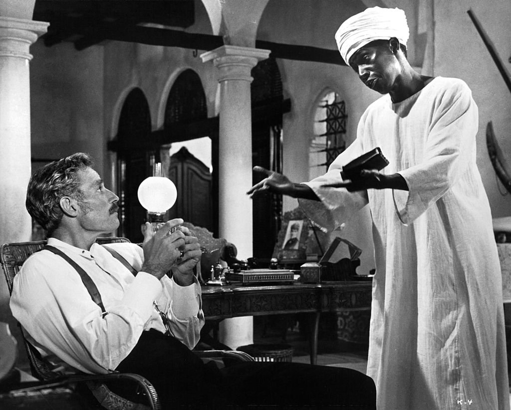 Charlton Heston sitting in a chair looking up at Johnny Sekka who is wearing a turban wrapped around his head in a scene from the film 'Khartoum', 1966. | Photo: Getty Images