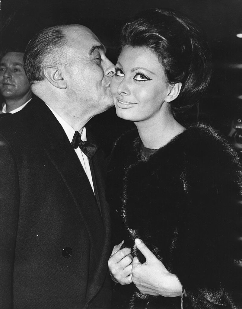 Italian film producer Carlo Ponti kisses his wife, actress Sophia Loren, after she received the first Alexander Korda award, naming her 'International Star of the Year', at the world premiere of her new film 'Lady L' at The Empire on November 26, 1965 | Photo: Getty Images