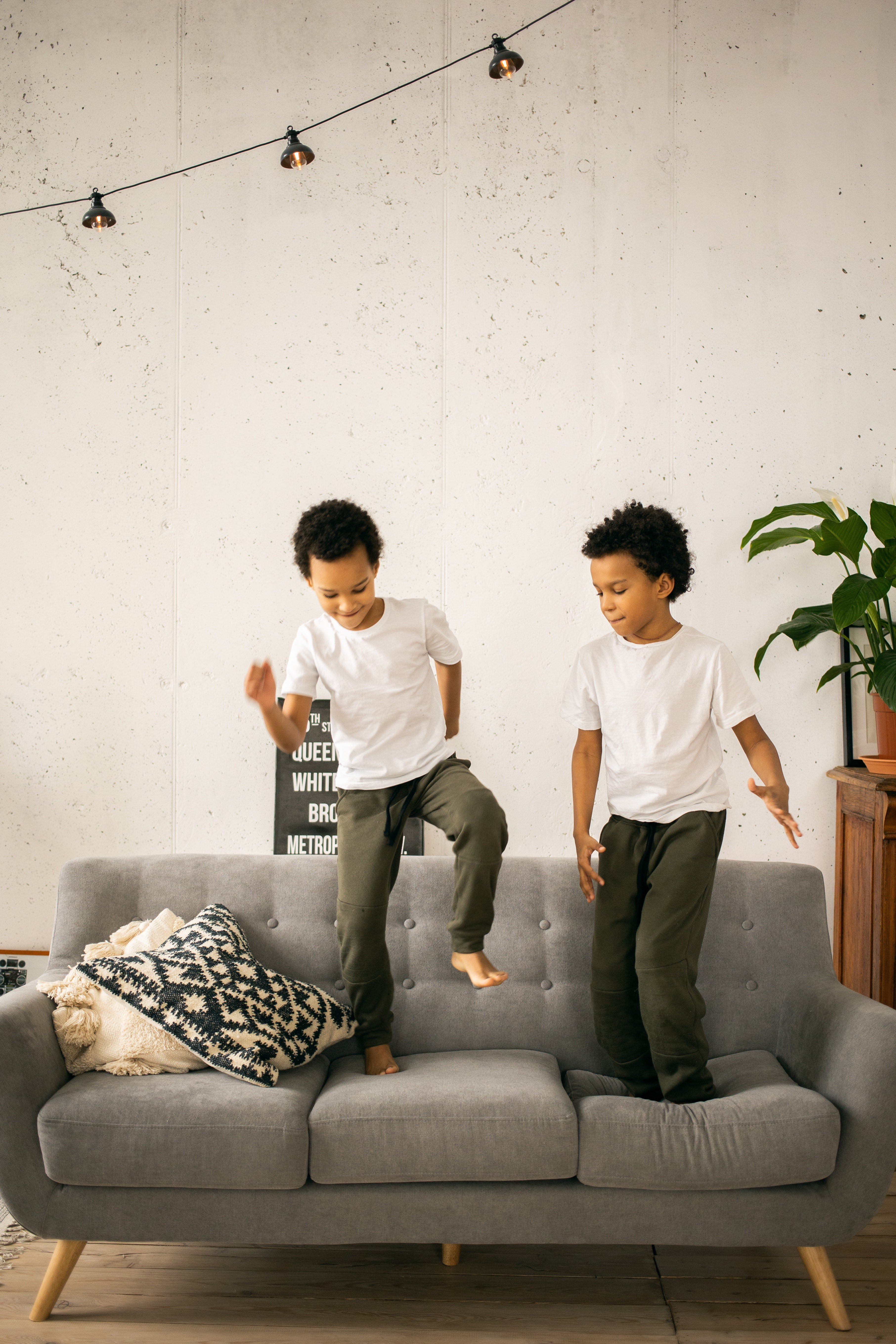 Identical twins jumping on the sofa   Photo: Pexels