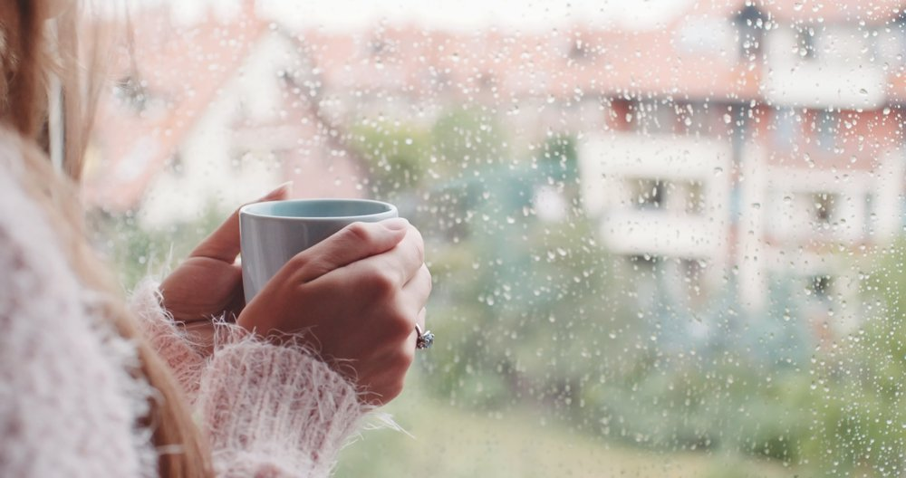 A photo of a woman with a cup of coffee looking out the window. | Photo: Shutterstock.