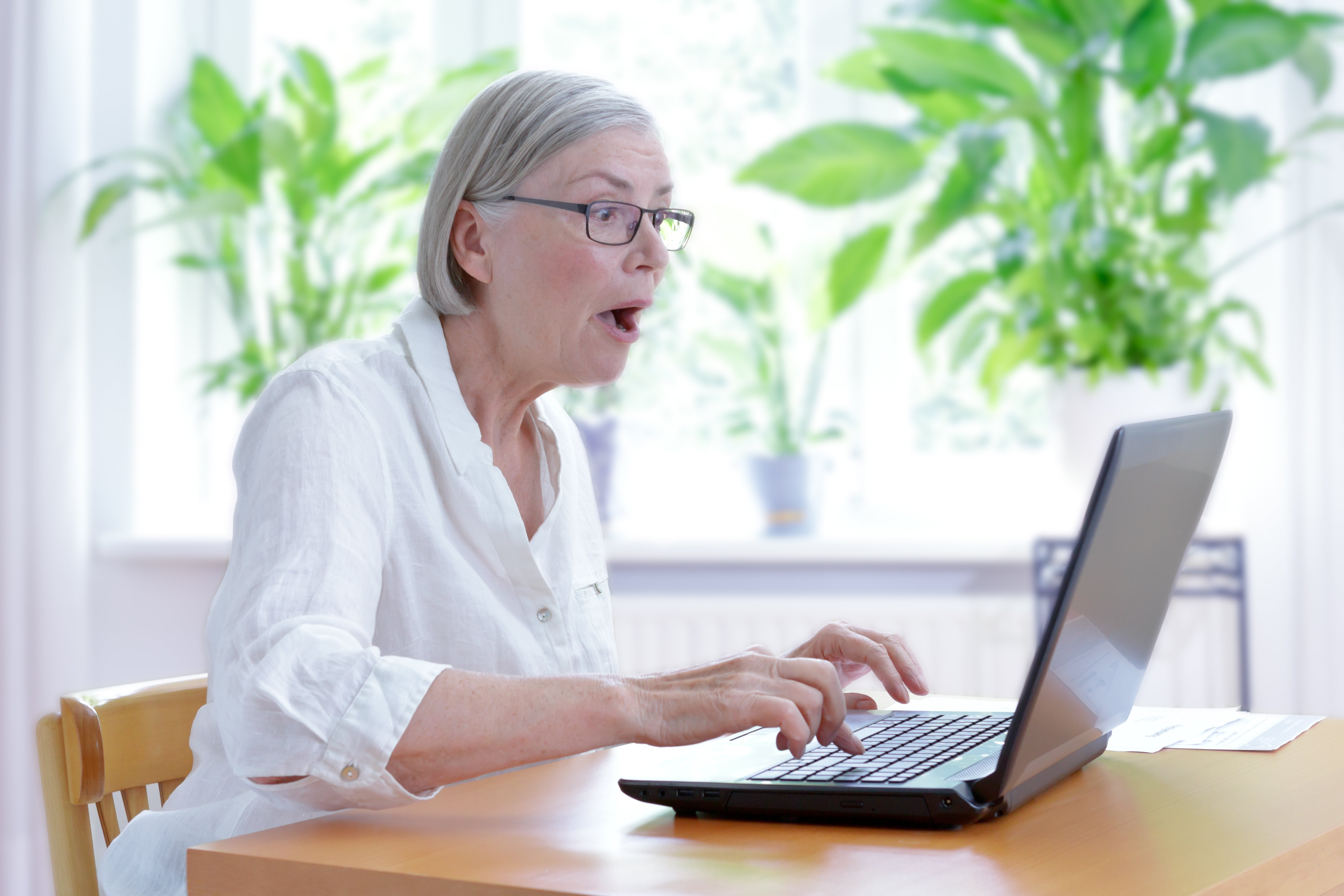 Elderly woman shocked while staring at laptop screen.   Source: Shutterstock
