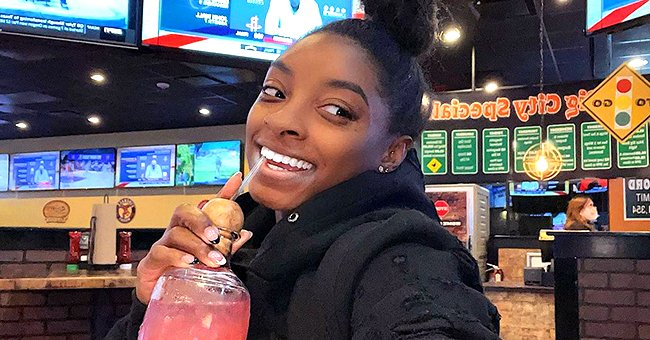 See Simone Biles' Casual Look As She Poses In a Mirror Selfie Wearing a White Tank Top & Pants