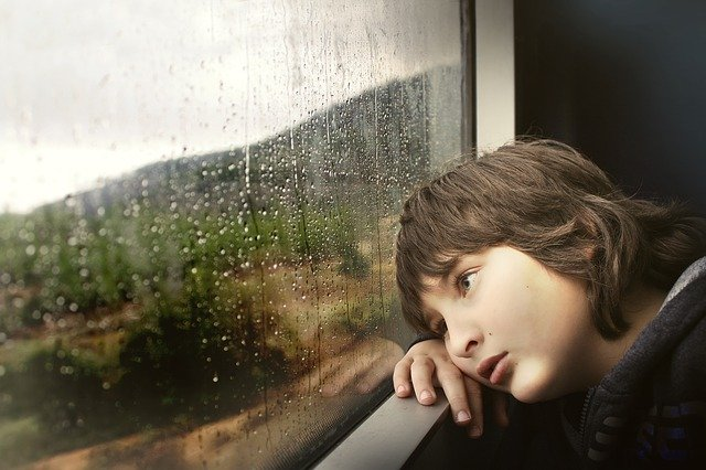 Boy looks out window as rain falls | Photo: Pixabay