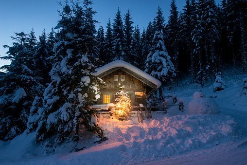 Snowman and Christmas tree at illuminated wooden house in snow at night | Photo: Getty Images